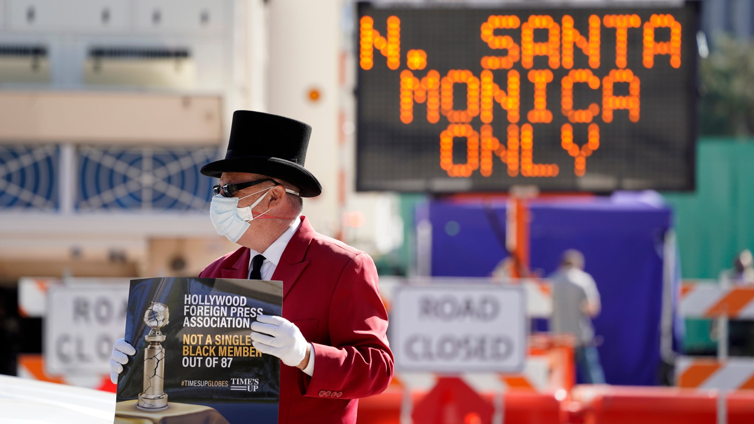 Gregg Donovan demonstrates with a sign protesting the lack of Black members in the Hollywood Foreign Press Association, outside a road closure near the 78th Golden Globe Awards at the Beverly Hilton, Sunday, Feb. 28, 2021, in Beverly Hills, Calif. (AP Photo/Chris Pizzello)