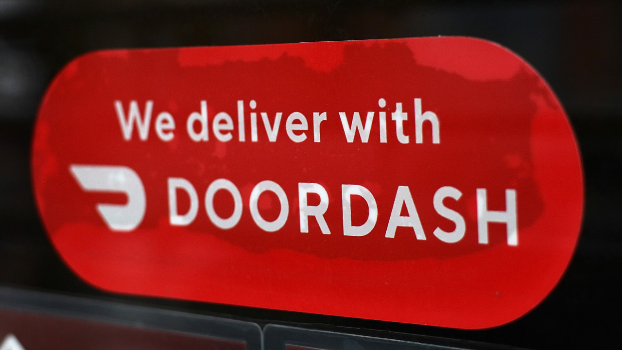 A Doordash sticker is seen on a window of a restaurant. (Photo by Michael M. Santiago/Getty Images)