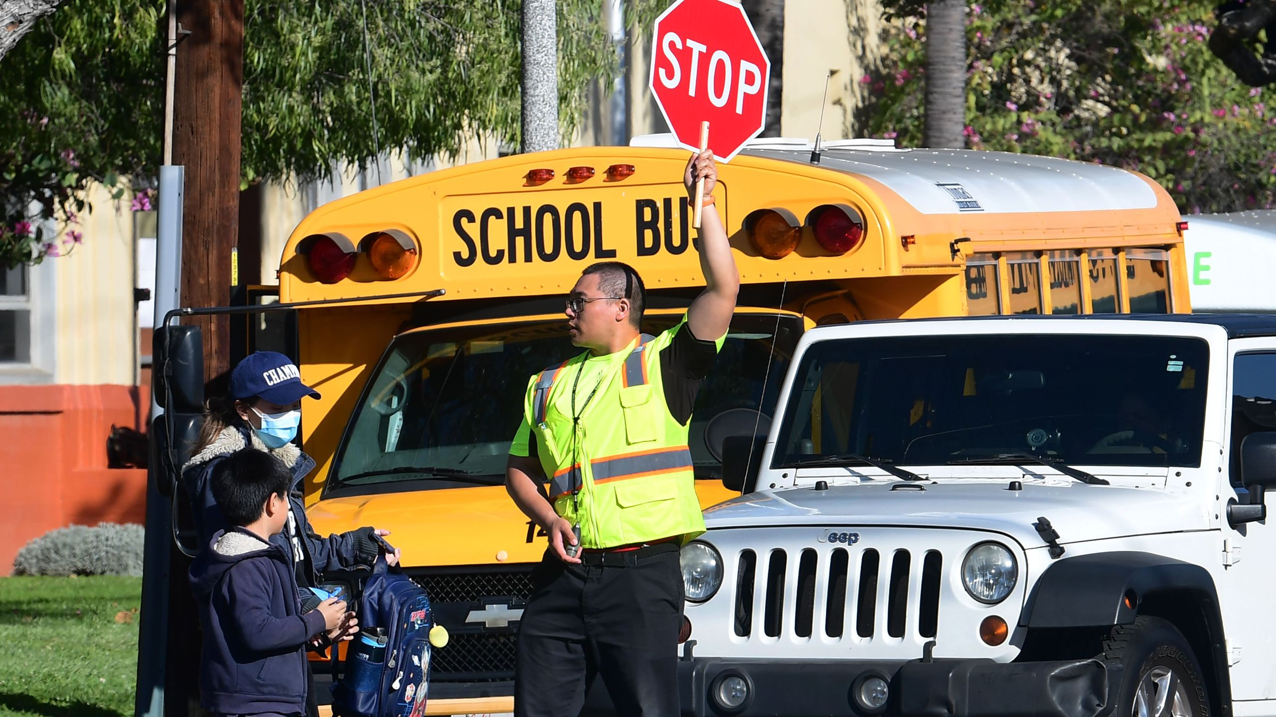 A woman wears a facemask picking up a child as an Alhambra Unified School District crossing guard stops traffic outside Ramona Elementary School on February 4, 2020 in Alhambra, California. (Photo by Frederic J. BROWN / AFP)