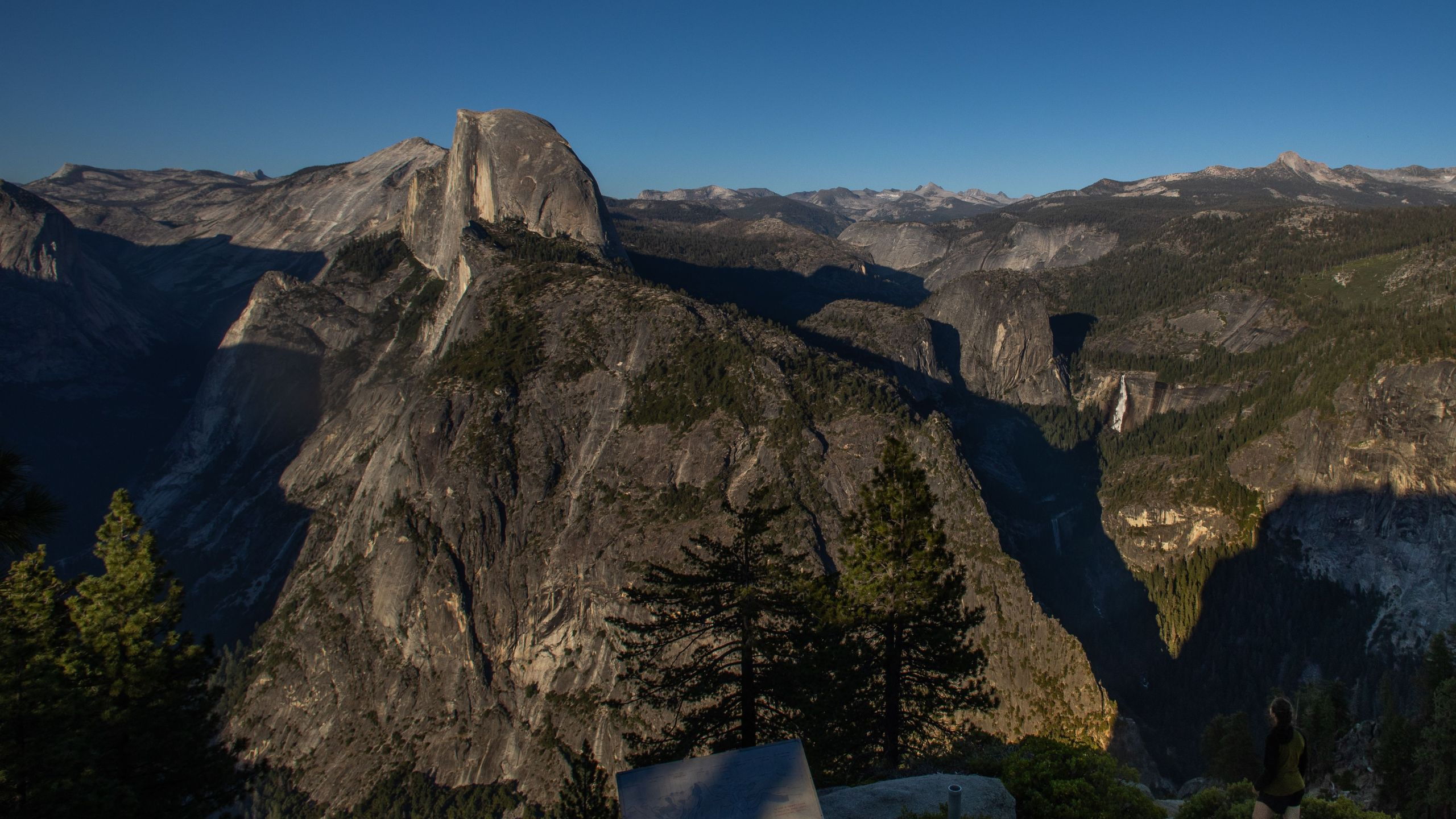 A visitor looks at Yosemite Valley including Half Dome (C L) and Nevada Fall (C R) from the Glacier Point in Yosemite National Park, California on July 06, 2020. (Apu Gomes/AFP via Getty Images)