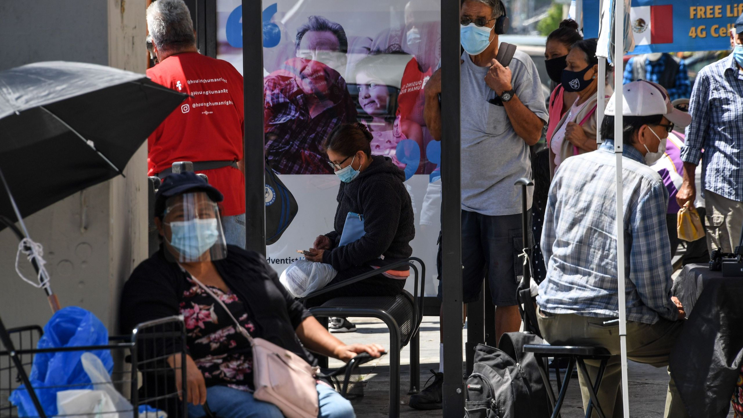 People wait for a bus in a neighborhood of East Los Angeles, Aug. 7, 2020 in Los Angeles, California during the coronavirus pandemic. (Robyn Beck/AFP via Getty Images)