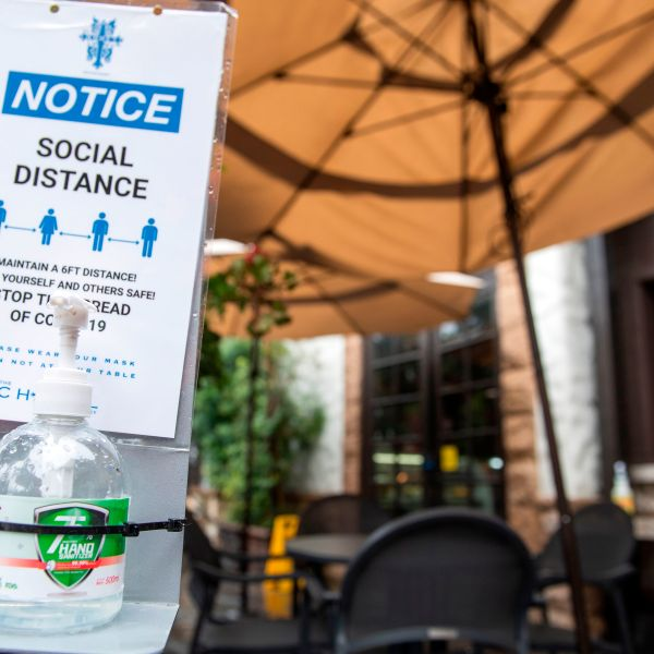 A notice calling for patrons to social distance along with hand sanitizer are seen in the outdoor seating area of The Abbey Food & Bar on January 29, 2021 in West Hollywood, California. (VALERIE MACON/AFP via Getty Images)