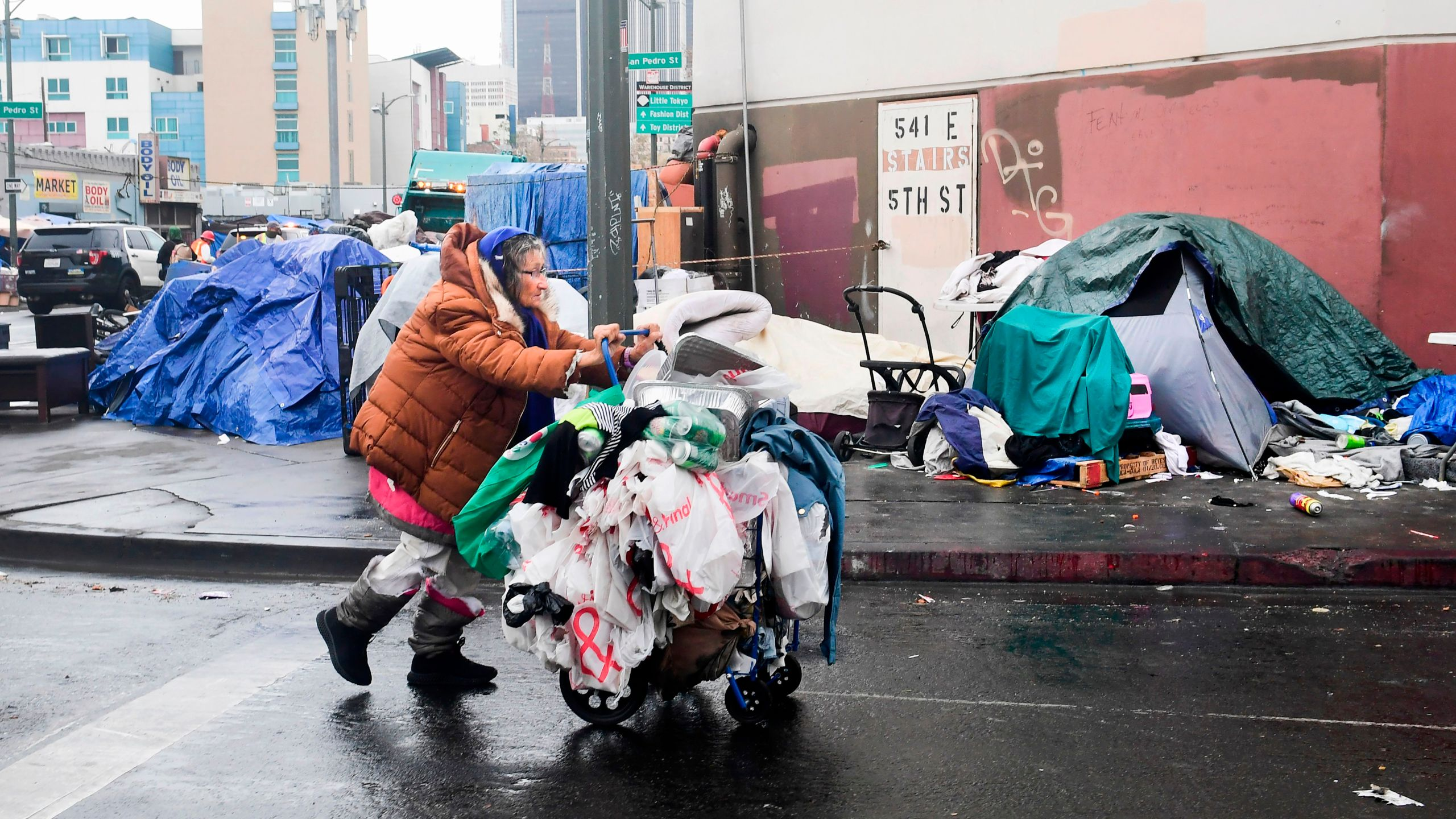 A homeless woman pushes her belongings past a row of tents on the streets of Los Angeles on Feb. 1, 2021. (Frederic J. Brown / AFP / Getty Images)