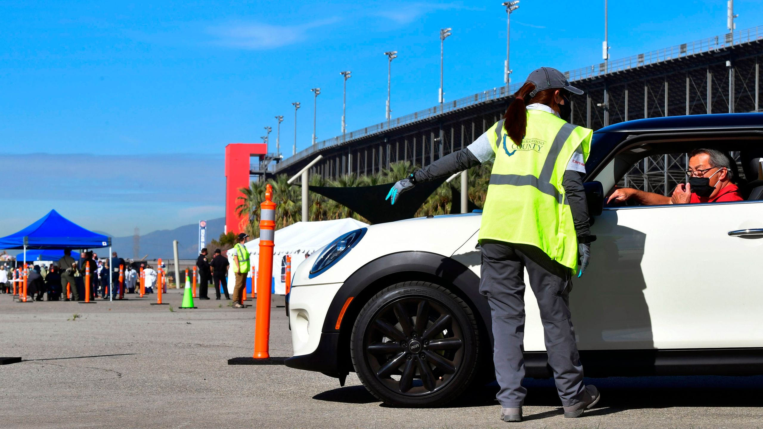 People arrive for their COVID-19 vaccine at the Auto Club Speedway in Fontana on Feb. 2, 2021. (Frederic J. Brown / AFP / Getty Images)