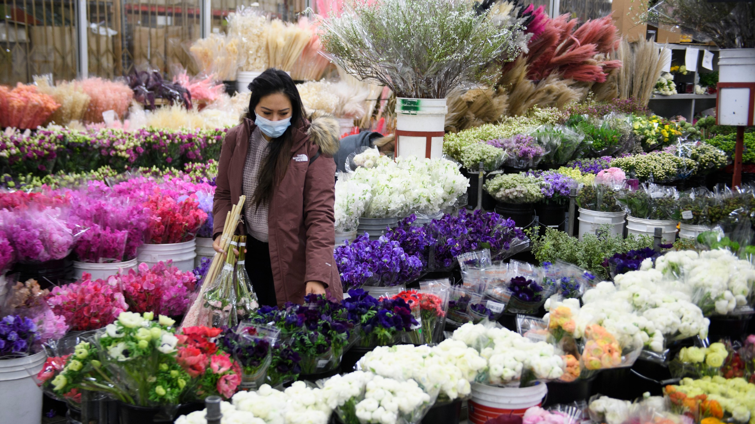 A customer wears a face mask while shopping for flowers displayed for sale from a wholesale merchant ahead of the Valentine's Day holiday at the Southern California Flower Market on Feb. 12, 2021 in Los Angeles. (PATRICK T. FALLON/AFP via Getty Images)