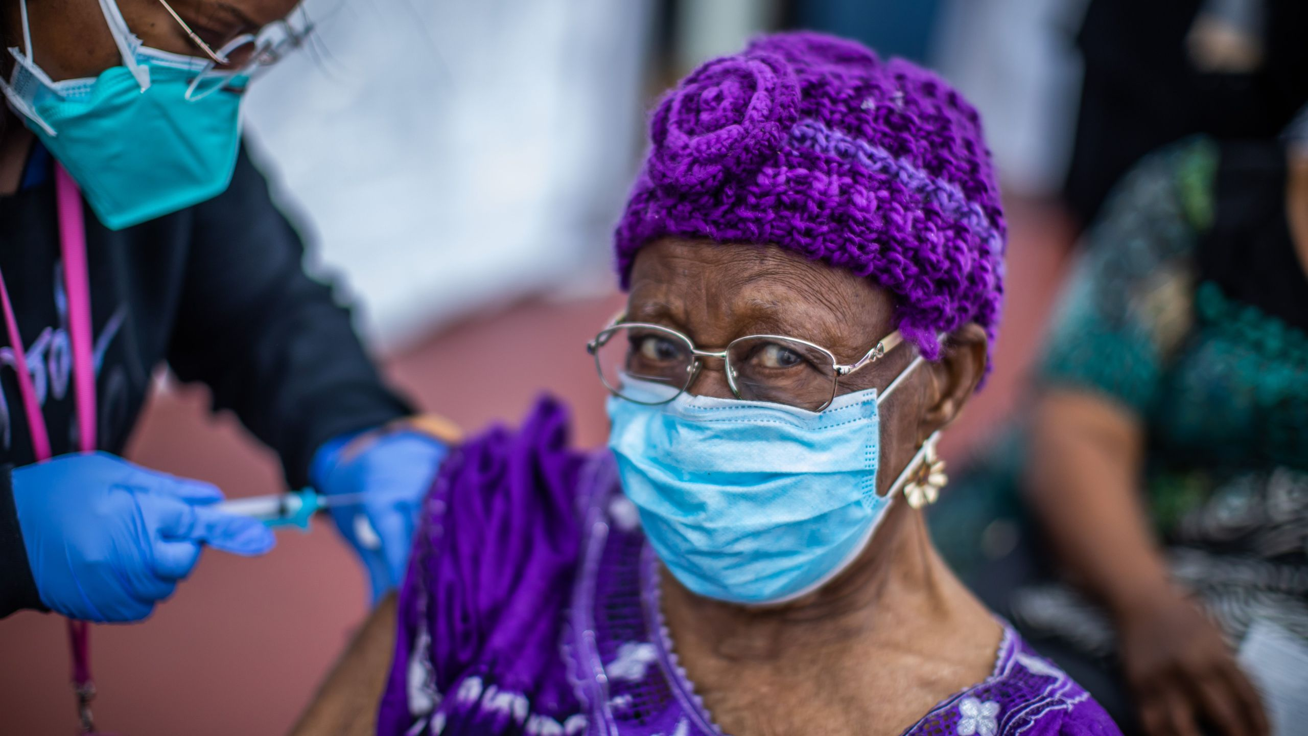 Registered Nurse Ebony Thomas administers a COVID-19 vaccine to Cecilia Onwytalu, 89, at the Kedren Community Health Center in South Los Angeles on Feb. 16, 2021. (Apu Gomes / AFP / Getty Images)