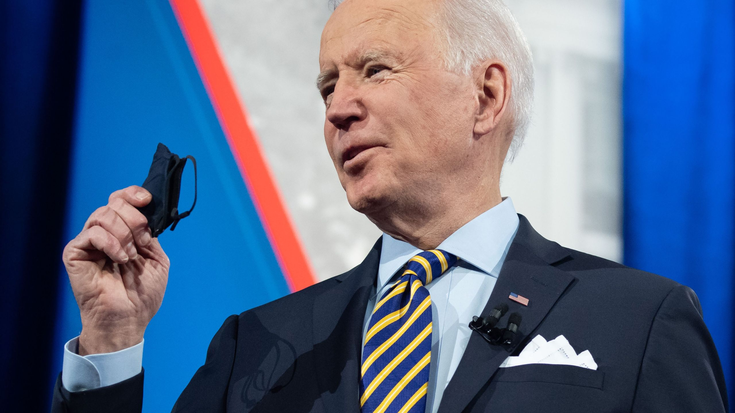 President Joe Biden holds a face mask as he participates in a CNN town hall at the Pabst Theater in Milwaukee, Wisconsin, on Feb. 16, 2021. (Saul Loeb / AFP / Getty Images)