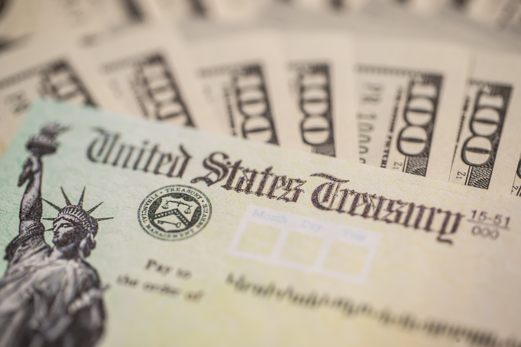 A check from the U.S. Treasury Department and cash are seen in a file photo. (iStock/Getty Images Plus)