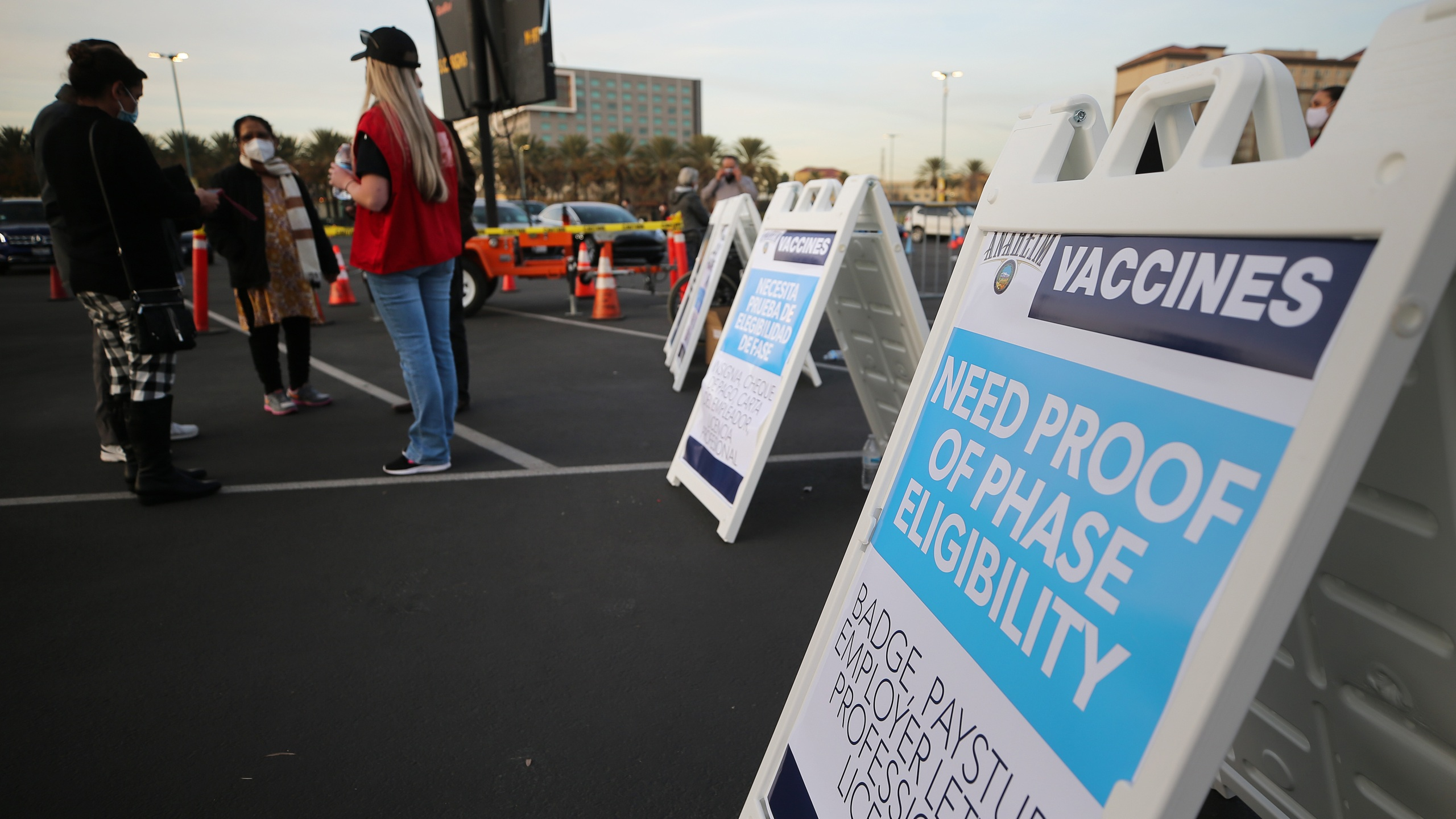 A sign is posted about proof of eligibility at a mass COVID-19 vaccination site in a parking lot of Disneyland Resort in Anaheim on Jan. 13, 2021. (Mario Tama / Getty Images)