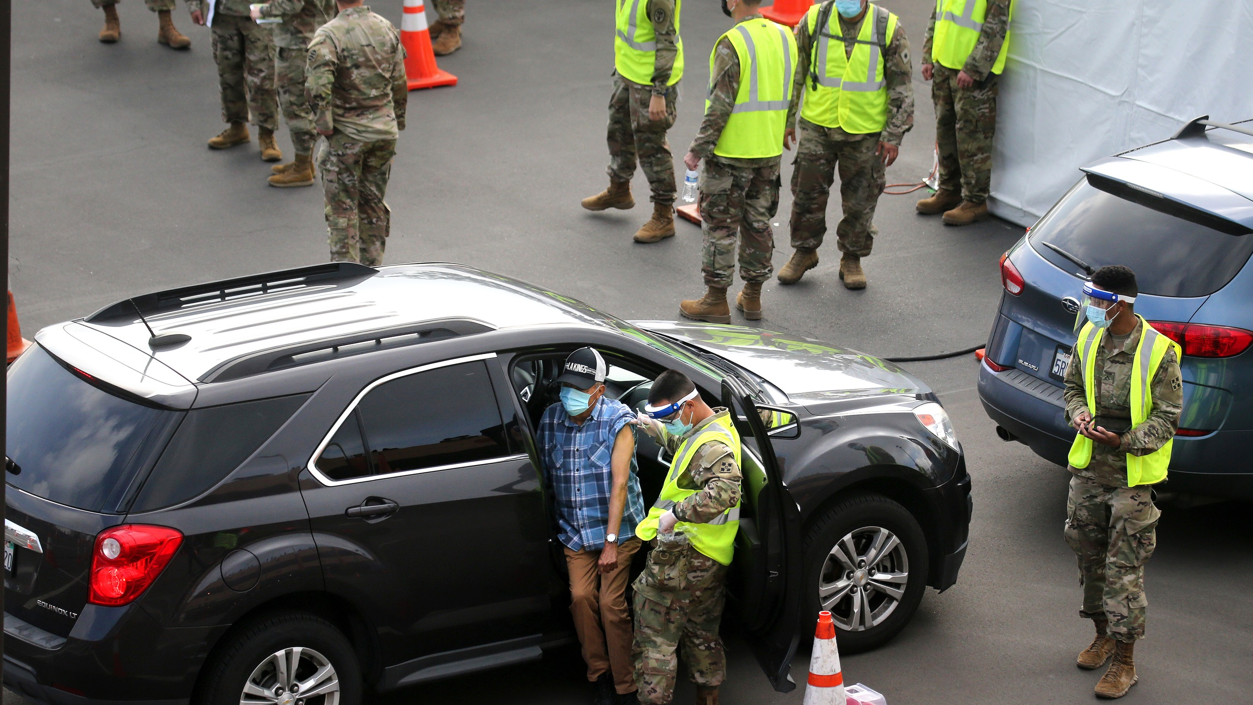 A person is vaccinated by a member of the National Guard at a new large scale COVID-19 vaccination site at Cal State Los Angeles on Feb. 16, 2021. (Mario Tama/Getty Images)
