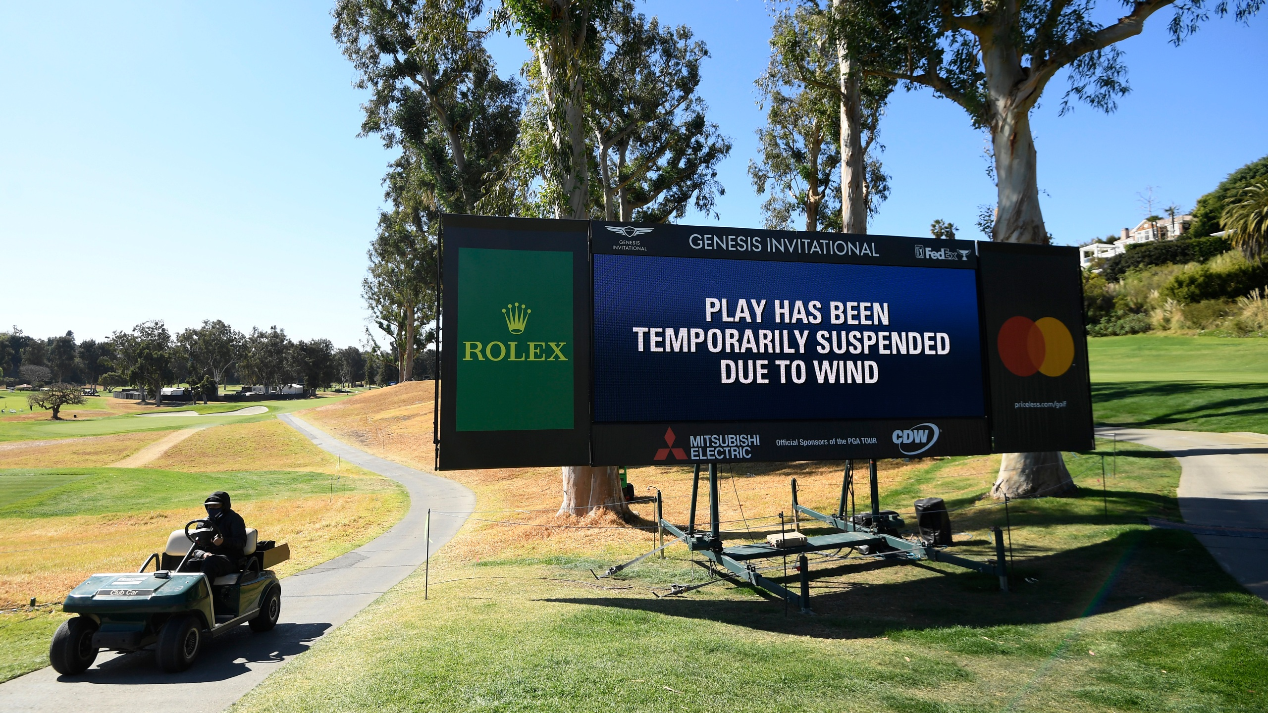 "A video board displaying the message ""Play Has Been Temporarily Suspended Due to Wind"" is seen during the third round of The Genesis Invitational at Riviera Country Club on Feb. 20, 2021 in Pacific Palisades. (Harry How/Getty Images)"