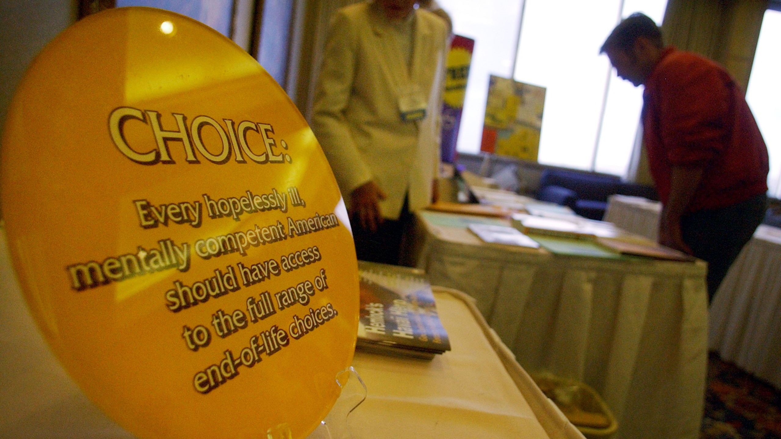 """A sign promoting promoting assisted suicide is displayed at the Hemlock Society's annual meeting being held at the Bahia resort Jan. 10, 2003 in San Diego, California. The society advocates """"choice and dignity at the end of life,"""" according to its Website. (Sandy Huffaker/Getty Images)"""