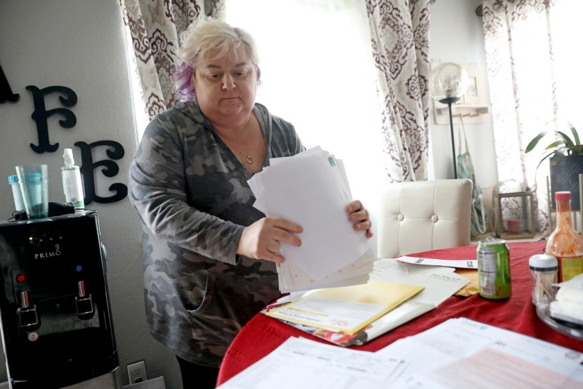 Patricia Mason, 51, displays her medical bills at her home in Vacaville, Calif. Mason works more than full time across two jobs — office administrative work, which she can do from home, and retail, which she can't.(Gary Coronado / Los Angeles Times)