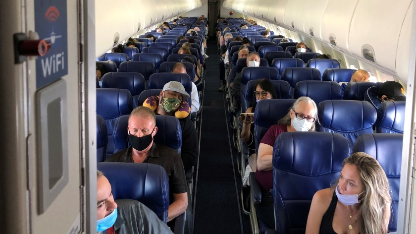 Passengers wear masks — some with their noses peeking out — on a June 3 flight. Under CDC guidelines, masks must completely cover the wearer's nose and mouth. (Christopher Reynolds / Los Angeles Times)