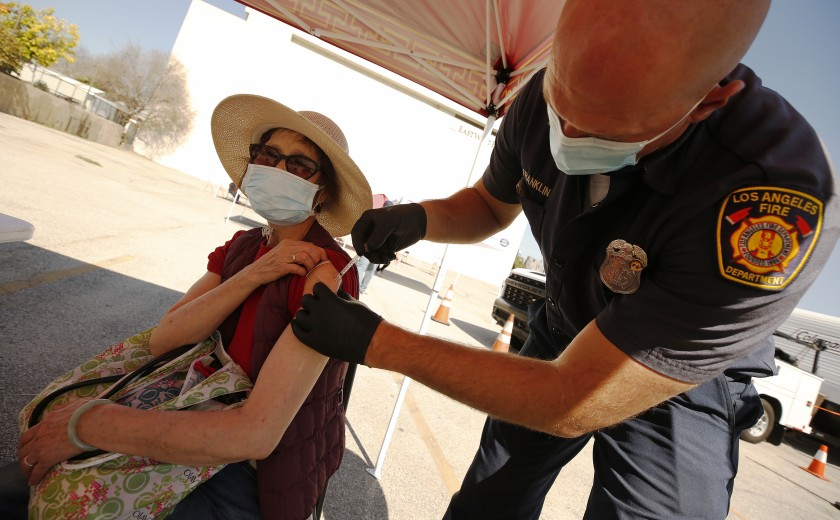 Yuyao Lui, 76, receives a COVID-19 vaccine shot from Joseph Franklin, an L.A. firefighter and paramedic, at a clinic in Chinatown in an undated photo. (Al Seib / Los Angeles Times)