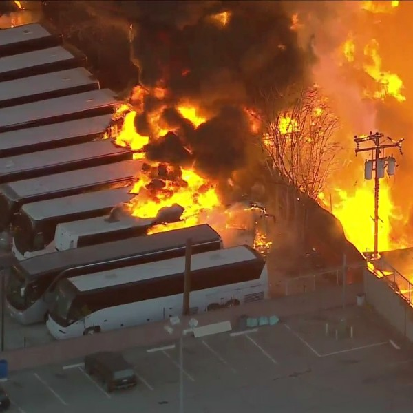 Flames reach a row of buses parked near an industrial complex in Compton on Feb. 26, 2021. (KTLA)
