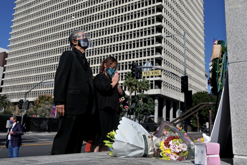Court interpreter Nao Ikeuchi, left, and wife Yoshimi Shirata attend a vigil to honor two court interpreters at Los Angeles Superior Court who died recently of COVID-19.(Gary Coronado / Los Angeles Times)
