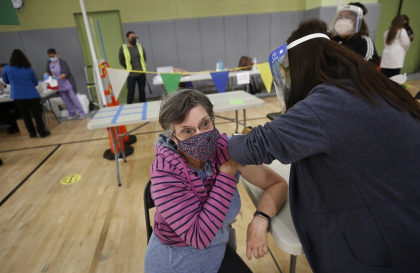 Los Angeles substitute teacher Jane Golliver, 67 receives her COVID-19 vaccination last week from Mary Ann Topico, right, in a pilot clinic at Roybal Learning Center, west of downtown, that provided 100 doses.(Al Seib / Los Angeles Times)