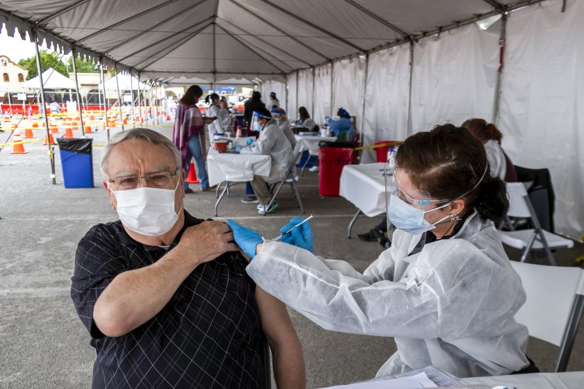 Robert Nelson, 81, of Riverside, left, gets a COVID-19 vaccine shot from nurse Susan Eyman in the parking lot of the Riverside Convention Center on Feb. 1, 2021. (Gina Ferazzi / Los Angeles Times)