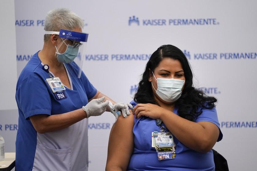 Nurse Helen Cordova, right, receives the Pfizer-BioNTech COVID-19 vaccine at Kaiser Permanente Los Angeles Medical Center. (Jae C. Hong / Associated Press )
