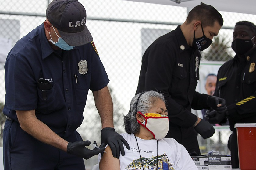 Firefighter Anthony MacDougall administers a COVID-19 vaccine to Carmen Limeta at a mobile vaccination site at South Park Recreation Center in Los Angeles.(Irfan Khan / Los Angeles Times)