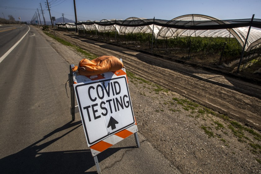 A sign points to COVID-19 testing available to farmworkers close to where they work near a hoop greenhouse in Oxnard in this undated photo. (Brian van der Brug / Los Angeles Times)