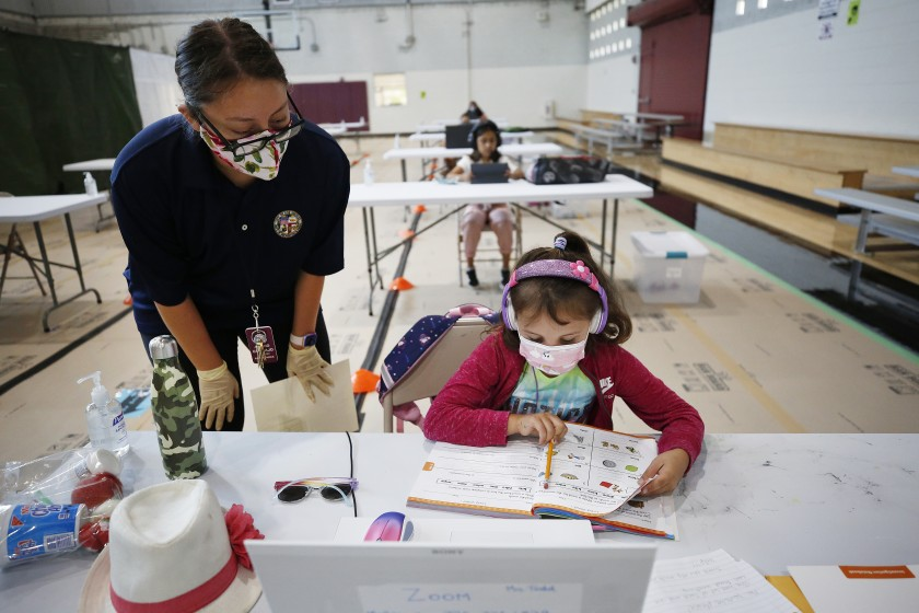 First-grader April Alvarez logs into online classes in September 2020 from the Delano Recreation Center in Van Nuys, with help from Astrid Gramajo. (Al Seib / Los Angeles Times)