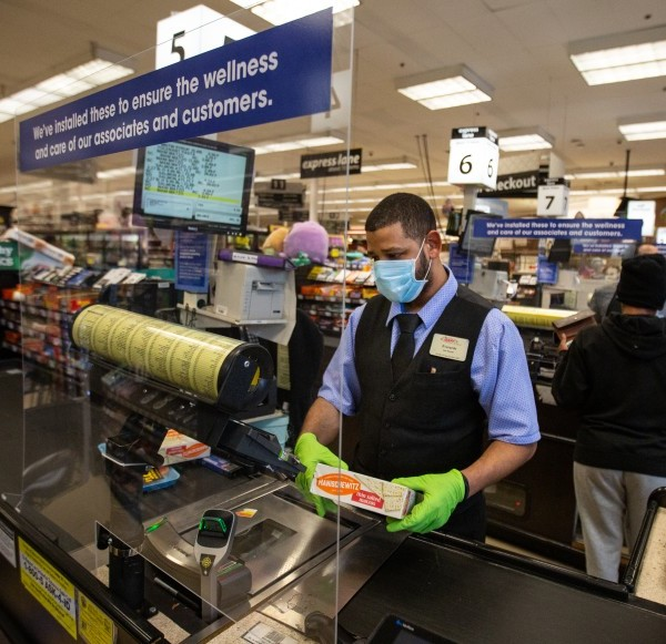 Everardo Gonzalez scans groceries behind a new plexiglass barrier at a Ralphs grocery store in Marina Del Rey during the coronavirus pandemic in April 2020.(Jason Armond / Los Angeles Times)