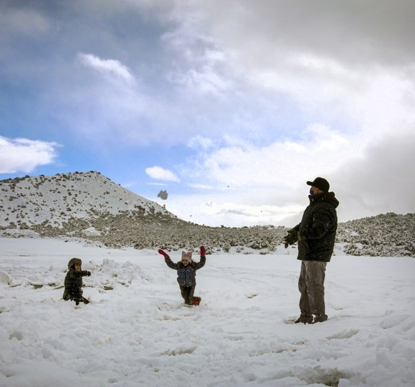 Adrian Rios, right, and his children, Ian Rios and Susan Rios, play in freshly fallen snow along Highway 138 in Phelan, Calif.(Irfan Khan / Los Angeles Times)