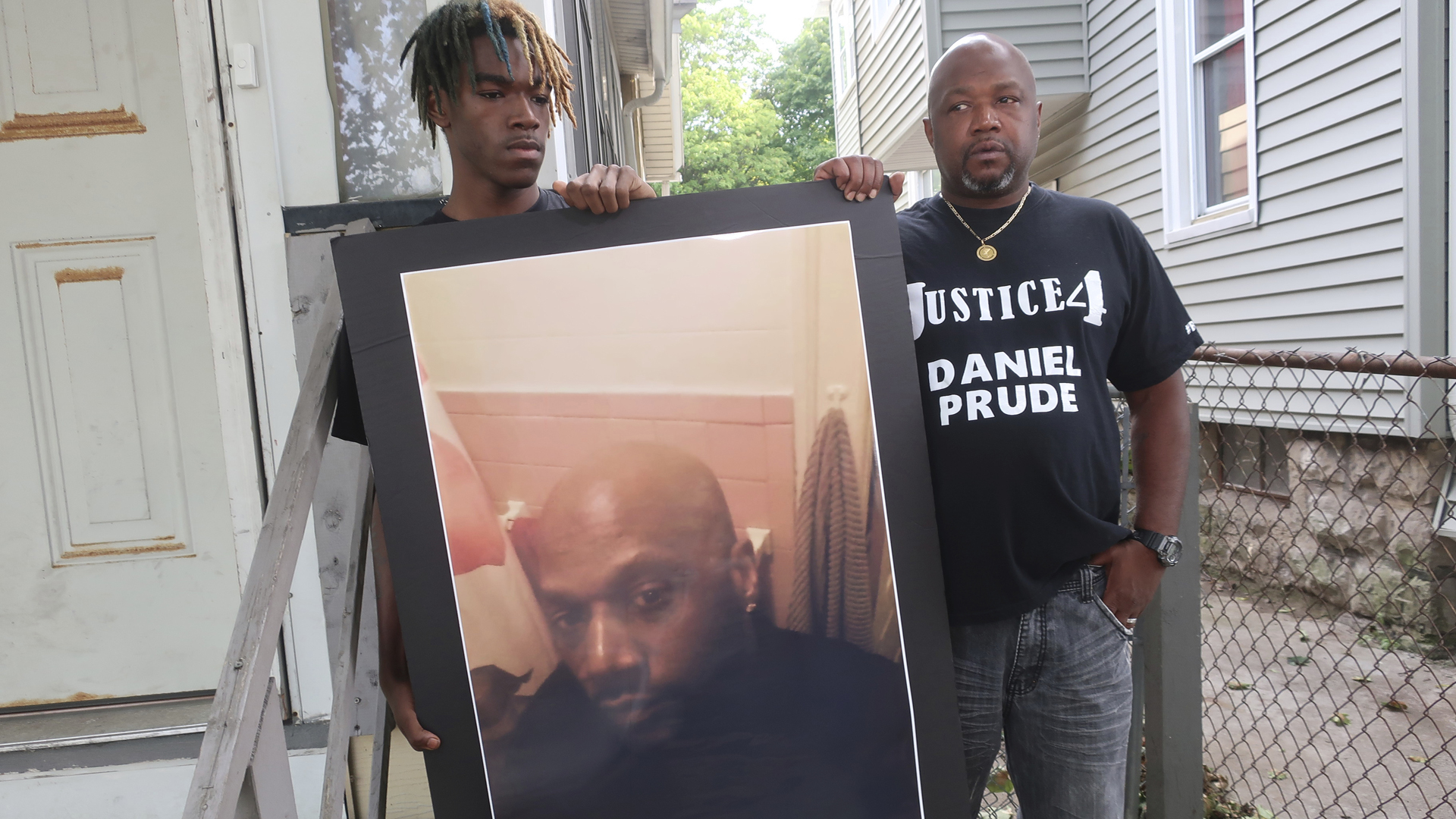 In this Sept. 3, 2020, file photo, Joe Prude, brother of Daniel Prude, right, and his son Armin, stand with a picture of Daniel Prude in Rochester, N.Y. (Ted Shaffre/Associated Press)