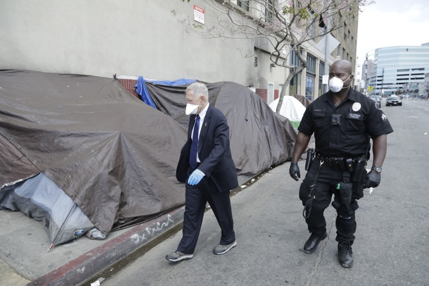 U.S. District Court Judge David O. Carter tours Los Angeles' skid row with LAPD Officer Deon Joseph in April 2020. (Myung J. Chun / Los Angeles Times)