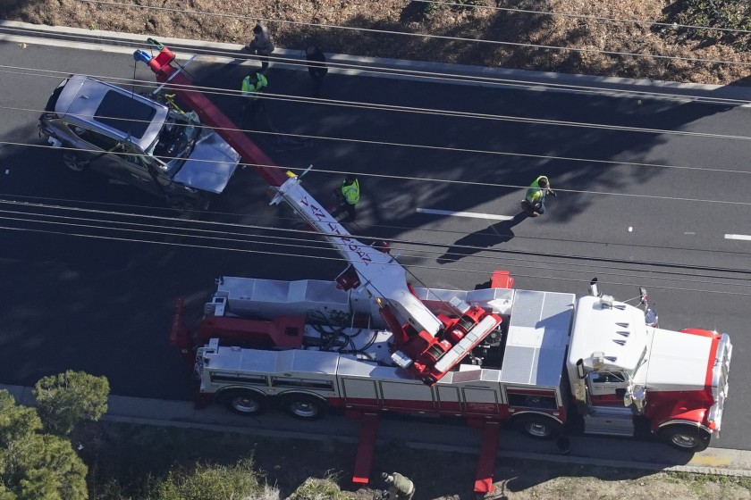 Workers use a crane to move a vehicle after a rollover accident involving golfer Tiger Woods on Tuesday in Rancho Palos Verdes, CA. (Mark J. Terrill / For The Times)