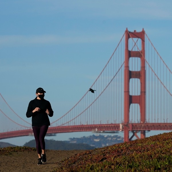 A person wearing a mask runs on a path in front of the Golden Gate Bridge in San Francisco during the coronavirus pandemic on Nov. 30, 2020. (Jeff Chiu / Associated Press)