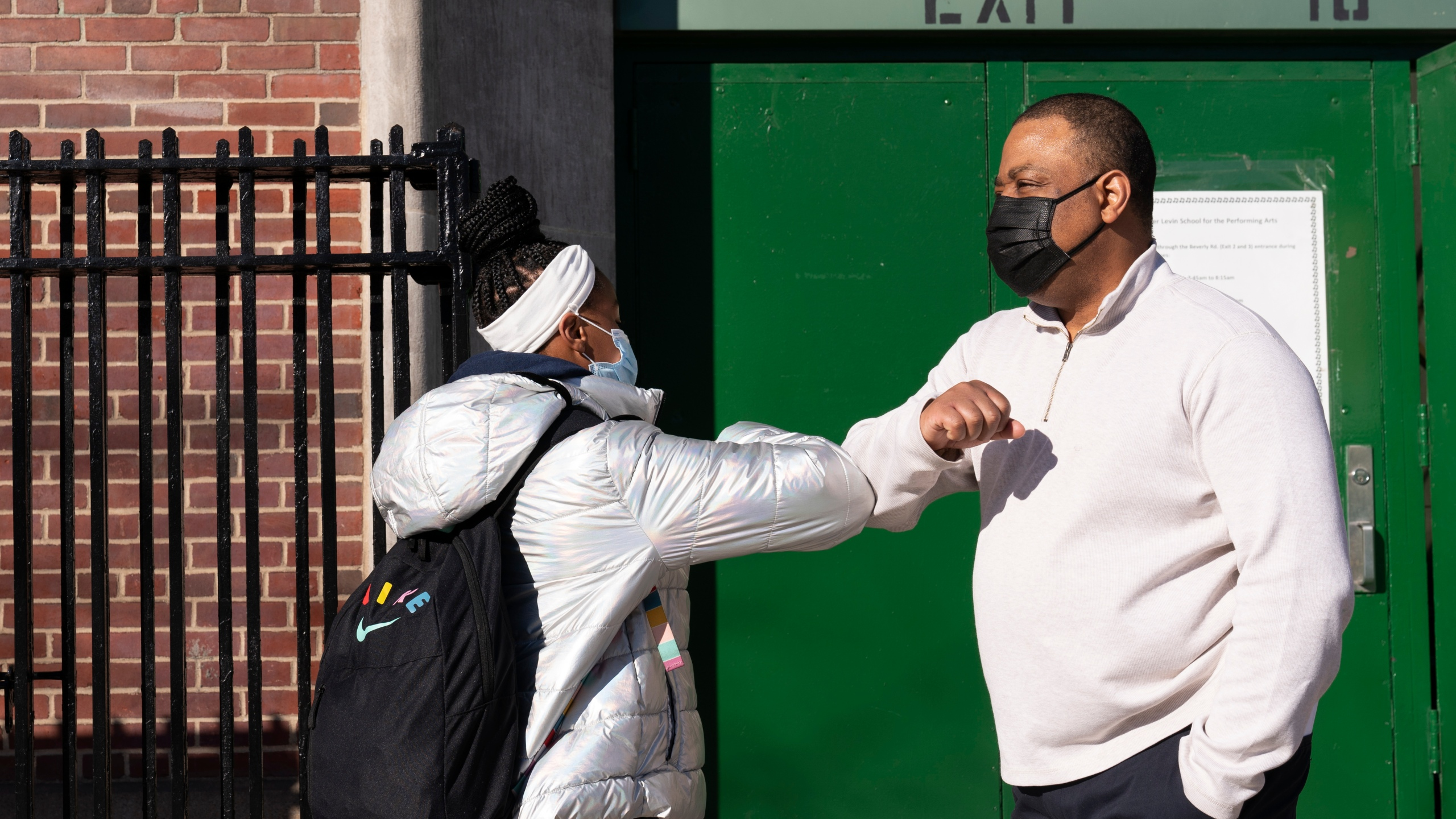 Linsey Johnson, right, a dean at Meyer Levin Middle School, greets a student, Thursday, Feb. 25, 2021, in New York. (AP Photo/Mark Lennihan)