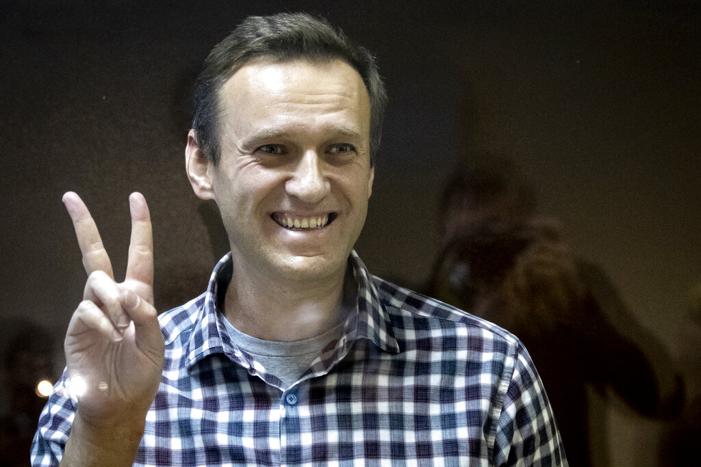 In this Saturday, Feb. 20, 2021 file photo, Russian opposition leader Alexei Navalny gestures as he stands behind a grass of the cage in the Babuskinsky District Court in Moscow, Russia. (AP Photo/Alexander Zemlianichenko, File)