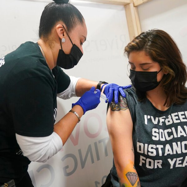 Denise Padilla, right, an instructor at the culinary school at Eva's Village, is vaccinated in Secacus, N.J., Sunday, Feb. 28, 2021. (AP Photo/Seth Wenig)