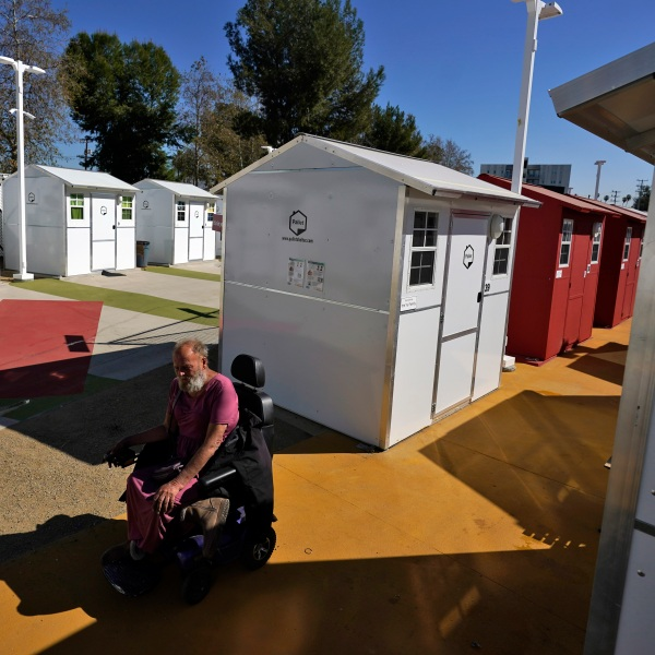 A homeless person rides by a row of tiny homes on Feb. 25, 2021, in North Hollywood. (AP Photo/Marcio Jose Sanchez)