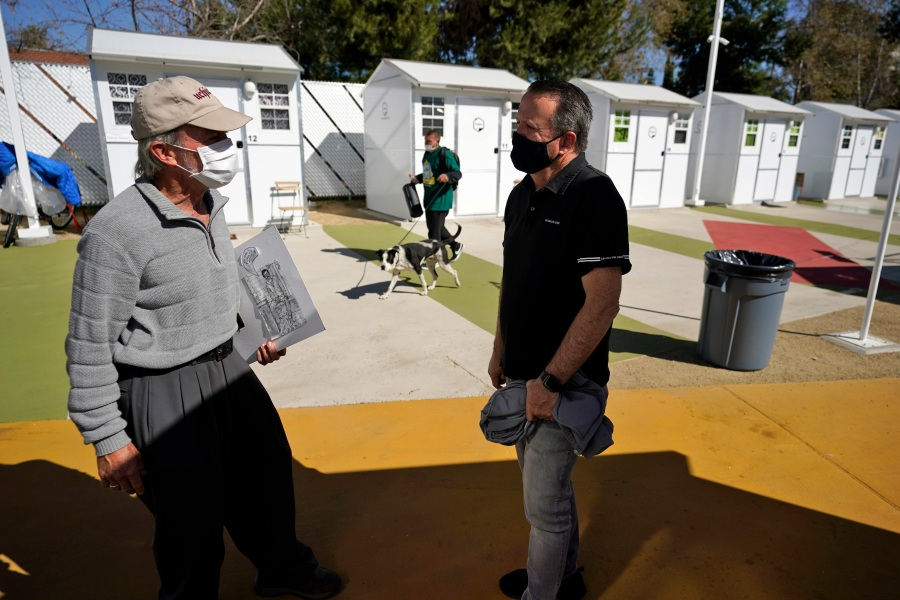 Hope of the Valley CEO Ken Craft, right, talks to resident Ted Beauregard outside of a row of tiny homes for the homeless on Feb. 25, 2021, in North Hollywood. (AP Photo/Marcio Jose Sanchez)