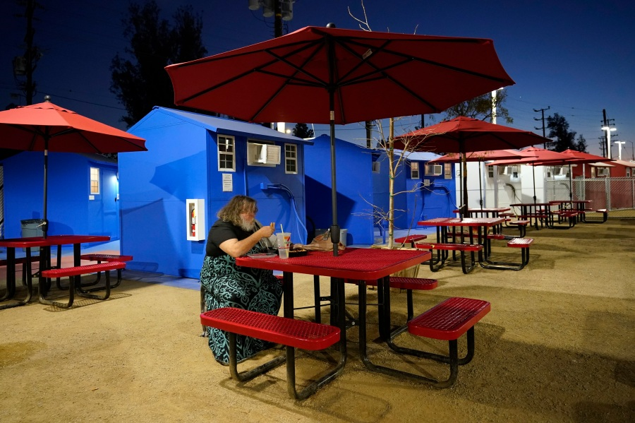 A resident eats in front of a row of tiny homes for the homeless on Feb. 25, 2021, in North Hollywood. (AP Photo/Marcio Jose Sanchez)