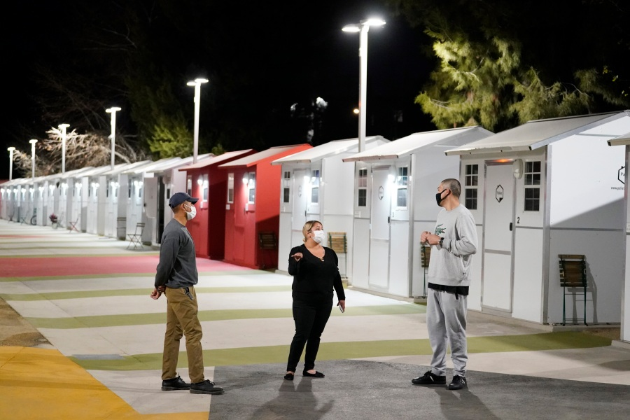 Workers talk to a resident, at right, in front a row of tiny homes for the homeless on Feb. 25, 2021, in North Hollywood. (AP Photo/Marcio Jose Sanchez)