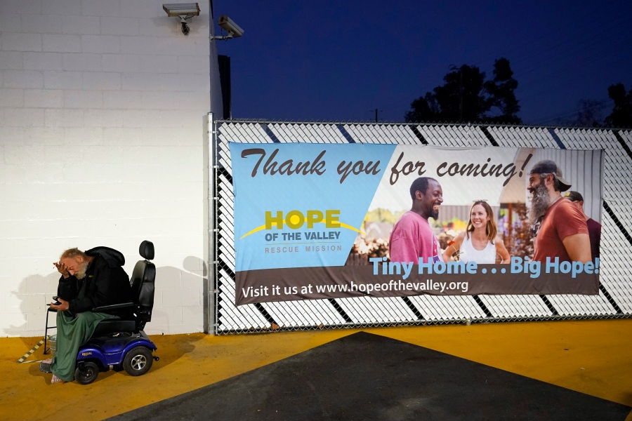 A homeless person, who calls himself Tiffany, at left, sits in a courtyard area in a tiny homes community for the homeless on Feb. 25, 2021, in North Hollywood. (AP Photo/Marcio Jose Sanchez)