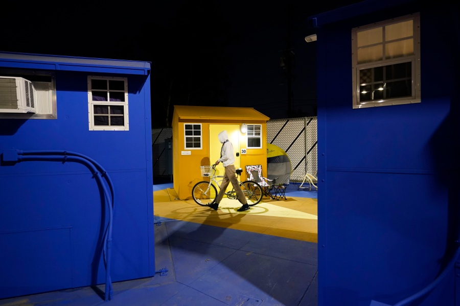 A resident walks with their bike along a row of tiny homes for the homeless on Feb. 25, 2021, in North Hollywood. (AP Photo/Marcio Jose Sanchez)