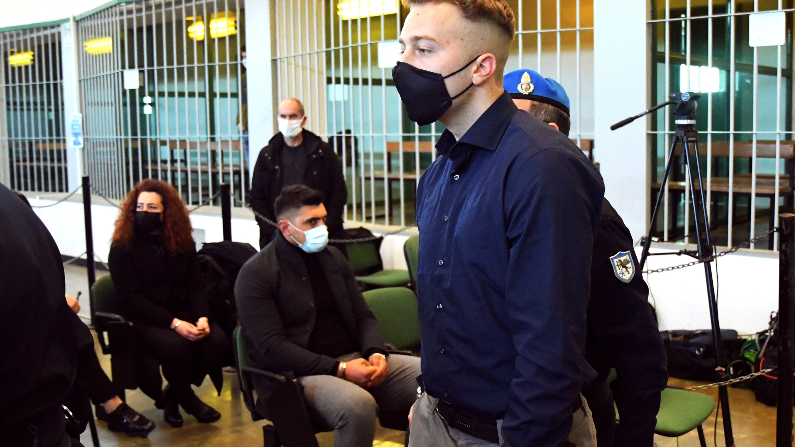 Finnegan Lee Elder, from the United States, walks past to Rosa Maria Esilio, widow of slain Carabinieri military police officer Mario Cerciello Rega, background left, and Paolo Cerciello Rega, brother of Mario, center, on March 1, 2021, prior to a hearing in Rome in the trial where he and Gabriel Natale-Hjorth are accused of slaying a plainclothes Carabinieri officer while on vacation in Italy in July 2019. (Alberto Pizzoli / Associated Press)