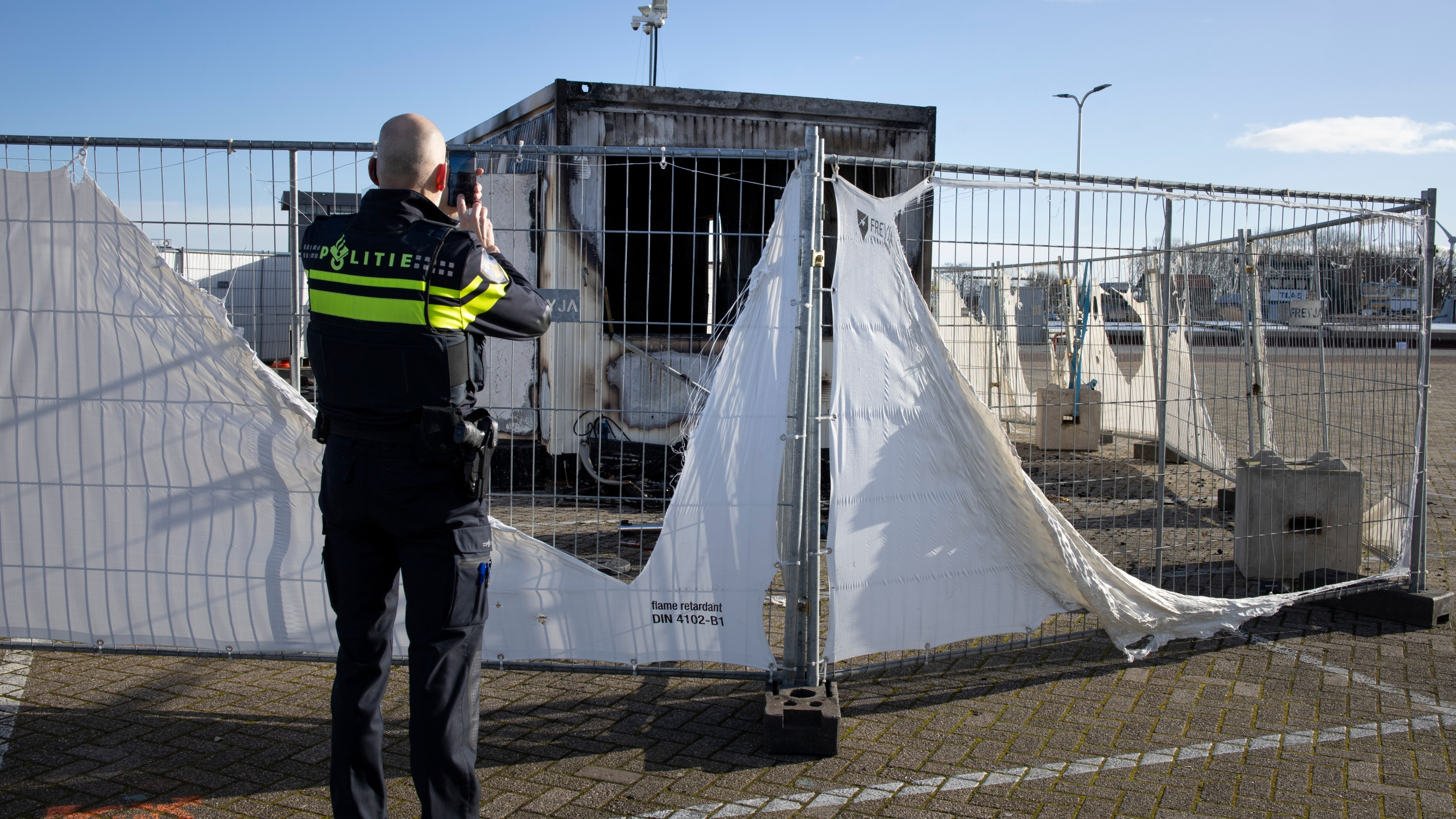 A police officer takes pictures of a burned-out coronavirus testing facility in the fishing village of Urk in the Netherlands on Jan. 24, 2021, after it was set on fire the night before by rioting youths protesting on the first night of a nationwide curfew. (Peter Dejong / Associated Press)
