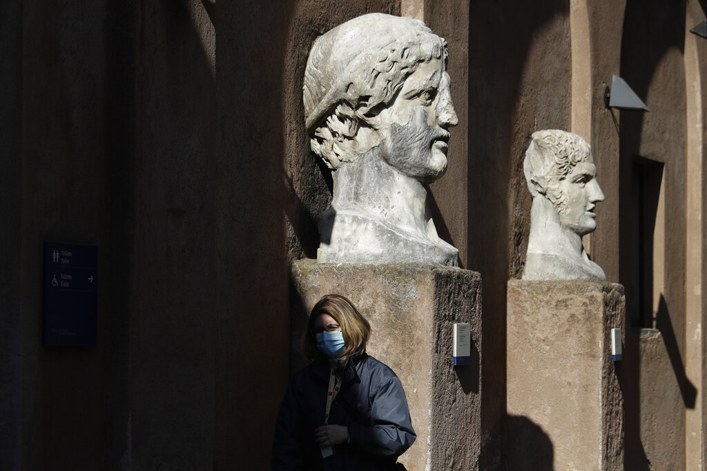 A museum usher stands by marble busts at the entrance of the Sant'Angelo castle In Rome Tuesday, March 2, 2021. (AP Photo/Gregorio Borgia)