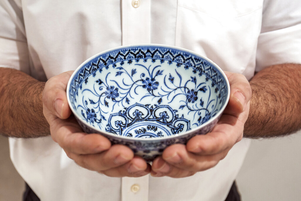 This photo, provided by Sotheby's, in New York, on Tuesday, March 2, 2021, shows a small porcelain bowl bought for $35 at a Connecticut yard sale that turned out to be a rare, 15th century Chinese artifact worth between $300,000 and $500,000. The bowl will be offered in Sotheby's Auction of Important Chinese Art, in New York, on March 17. (Sotheby's via AP)