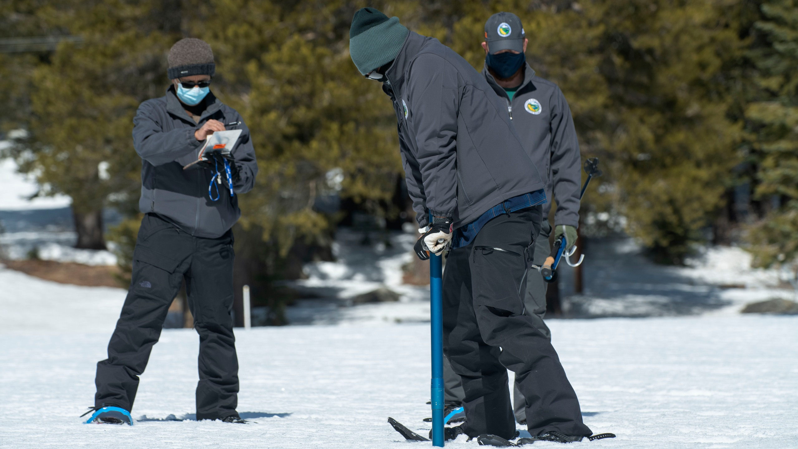 Assisted by Ramesh Gautam, left, and Anthony Burdock, right, Sean de Guzman, chief of snow surveys for the California Department of Water Resources, checks the depth of the snowpack during the second snow survey of the season at Phillips Station near Echo Summit on March 2, 2021. (Randall Benton / Associated Press)