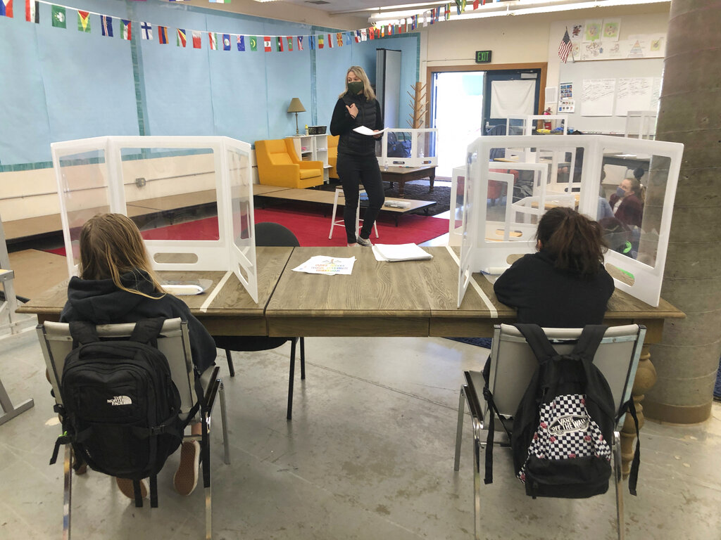 Jennifer Becker, center, Science Teacher, at the Sinaloa Middle School while masked talks her students who are distanced at their desks in Novato, Calif., on Tuesday, March 2, 2021. The school just reopened Monday, Feb. 22, 2021, for in-person learning. (AP Photo/Haven Daily)