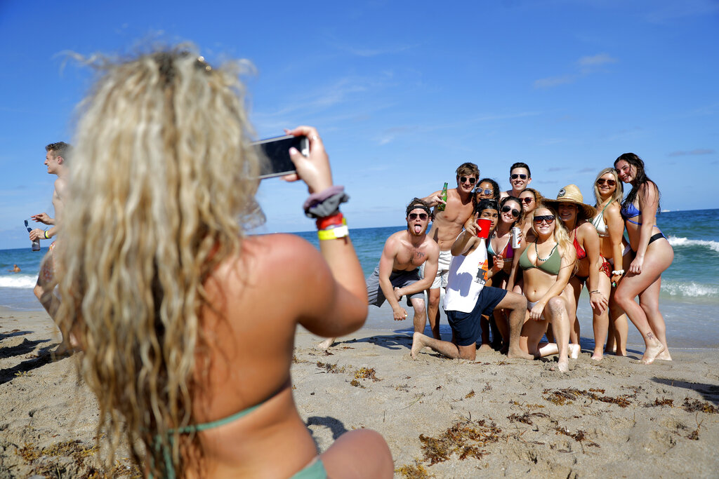 In this March 17, 2020, file photo, group of spring break revelers pose for a photograph on the beach in Pompano Beach, Fla. (AP Photo/Julio Cortez, File)
