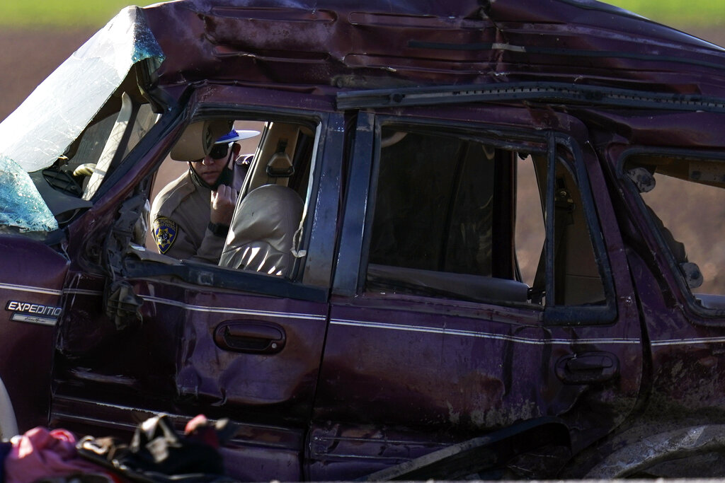 A California Highway Patrol officer examines the scene of a deadly crash in Holtville, Calif., Tuesday, March 2, 2021. (AP Photo/Gregory Bull)